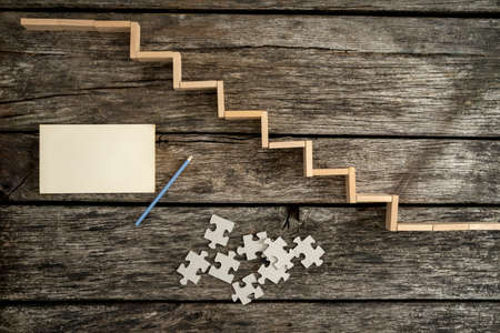 pencil and paper: Way to success - top view of wooden pegs forming a staircase on wooden desk with puzzle pieces, blank paper and a pencil lying next to it.