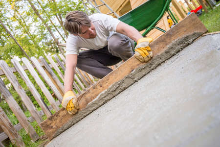 tilted view: Man leveling the cement in a backyard at home using a wooden plank as he lays a new concrete surface, low angle tilted view.