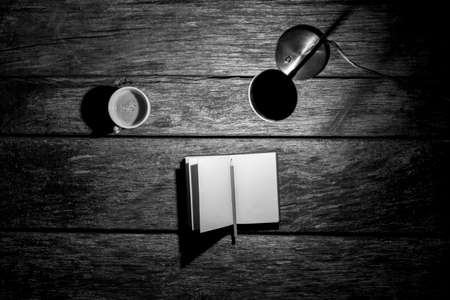 lit image: Top view of lit desk lamp, open notebook with pencil and cup of coffee on a textured wooden work desk, monochrome image.