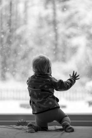 looking out: Black and white image of a toddler kneeling by the glass door inside the house looking out at snowflakes falling from the sky.