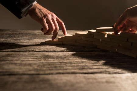 Close-up van de zakenman het regelen van houten pennen in een trappenhuis achtige structuur voor zijn collega aan zijn vingers lopen de trap op. Conceptuele zakelijke samenwerking, visie en succes. Stockfoto