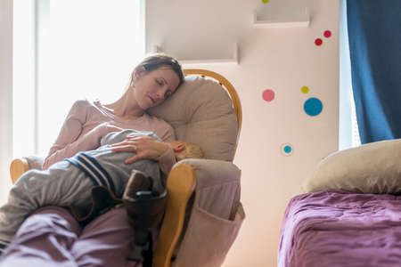 Tired young mother resting or napping on a rocking chair with baby sleeping in her lap inside a nursery room at day.
