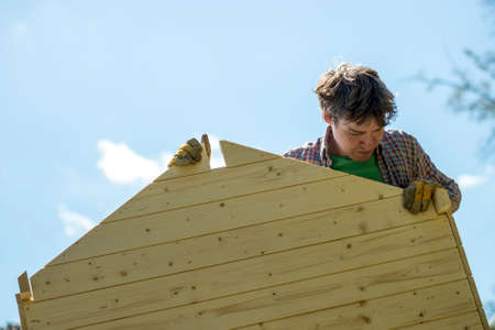 playhouse: Low angle view of a young man assembling a wooden playhouse in a DIY concept.