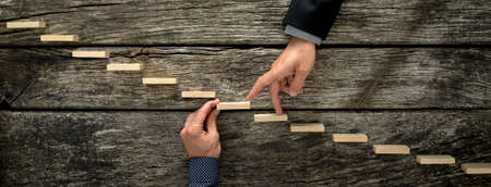 Hand of a businessman supporting a wooden step for his colleague to walk his fingers up towards success, conceptual of business teamwork and collaboration. Stock Photo
