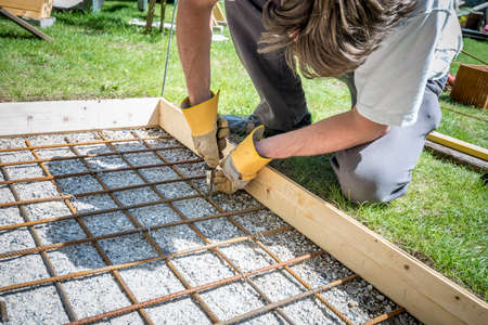 making hole: Closeup of a man making a net of steel bars by clipping them together with a wire and pliers placing it in as a reinforcement in a rectangular hole for a concrete foundation outside in backyard. Stock Photo
