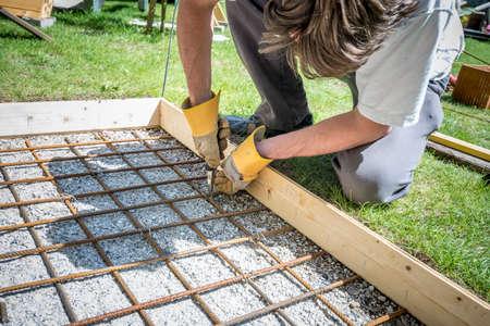 Hormigón: Primer plano de un hombre haciendo una red de barras de acero por el recorte de ellos junto con un alambre y pinzas colocándolo en como refuerzo en un agujero rectangular para una base de hormigón fuera en el patio trasero.