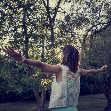 enjoying life: Woman standing in a park surrounded by trees with her arms spread widely enjoying life and nature, retro effect faded look. Stock Photo