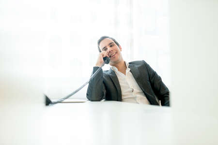 landline phone: Handsome young businessman sitting at his white office desk having a relaxed conversation on a landline phone with a big smile on his face.