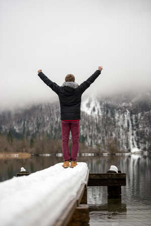 in low spirits: View from behind of a man raising his arms in triumph high in the air standing at the end of an old wooden pier covered with snow on a peaceful lake. Stock Photo