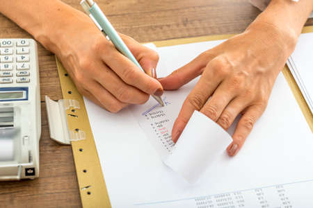 printout: Low angle view of female accountant summing up the numbers writing on a printout receipt while making financial report.