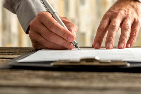hand pen: Front view of male hands signing document, contract or application form on a clipboard with ink pen, low angle view.
