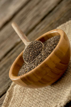 tilted view: Tilted view of small wooden bowl full of chia seeds and a wooden spoon on top, placed on linen cloth.