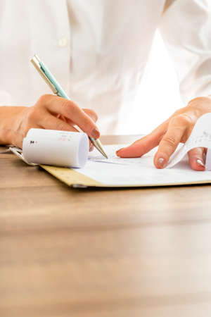 printout: Closeup of female hands making calculations or annual financial report writing end sum on a printout receipt with calculator alongside on wooden desk. Stock Photo