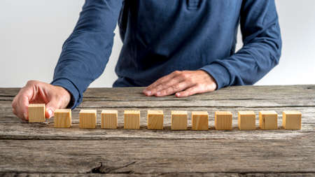 front desk: Front view of a man placing twelve blank wooden cubes in a row on a textured desk. Stock Photo
