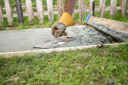 front  or back  yard: Low angle closeup view of a man with protective gloves leveling the surface of a concrete plate outside in back or front yard. Stock Photo