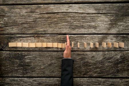 질감 된 나무 책상에 떨어지는 도미노를 중지하는 비즈니스 정장에서 남성 손의 상위 뷰. 위기 관리의 개념입니다.