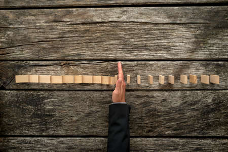 Bovenaanzicht van mannelijke hand in pak pakken vallende dominos op een getextureerde houten bureau. Conceptueel crisis management.