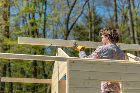 playhouse: Young man placing the main wooden beam to assemble a roof of a wooden playhouse outside in nature in a DIY concept.
