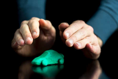 care allowance: Car insurance concept - male hands making protective gesture over a green car made of play dough on black desk with reflection. Over black background. Stock Photo