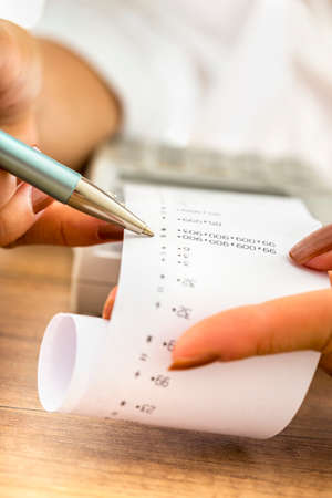 printout: Closeup of female accountant working by checking a printout or receipt coming out of adding machine looking at numbers holding a pen.