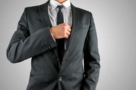 breast pocket: Businessman reaching inside his breast pocket of his suit to retrieve an item such as a business card, close up torso view in a suit.