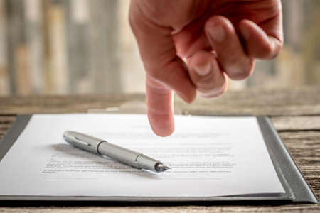 typed: Man pointing his finger to a typed document with a pen lying on top of it as he requests signature, close up view of his hand and paperwork. Stock Photo