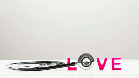 spelled: Love concept with the disc of a stethoscope forming the letter O in the word love spelled in vibrant pink letters with copy space on a light grey background.