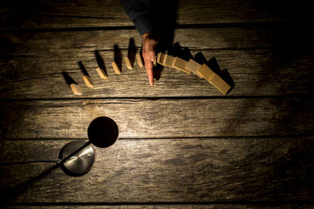 dominoes: Overhead view of a rustic wooden desk illuminated with a lamp with a seated man stopping the domino effect of falling dominoes by inserting a hand in their path in a conceptual image with copy space.