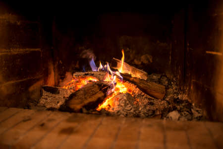 heaped: Wood fire with heaped hot ashes and flaming logs burning in a rustic open brick hearth in a low angle close up view.