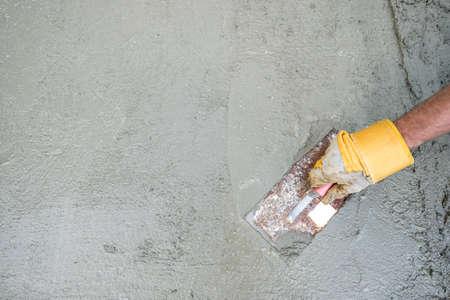 Arbeiter oder Baumeister beim Verputzen einer Betonoberfläche, Draufsicht auf seine Hand und sein Werkzeug in einem Heimwerker-, Renovierungs- und Baukonzept mit Kopierraum. Standard-Bild