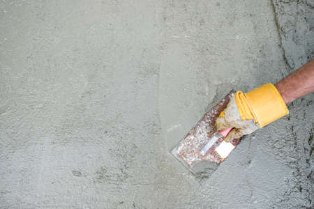 Workman or builder doing plastering of a concrete surface, top view of his hand and tool in a DIY, renovation and construction concept, with copy space. Standard-Bild