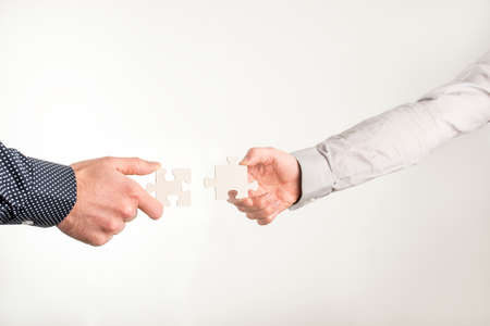 Two businessmen holding out puzzle pieces towards each other in a concept of team work, cooperation and collaboration, close up of their hands.