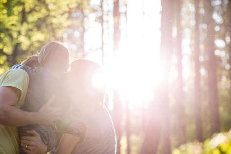 iluminado a contraluz: Abrazar Familia en maderas volver iluminada por la luz del sol radiante a través de árboles altos y con el espacio de la copia. Foto de archivo