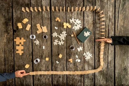 Top down view on hand blocking falling dominos surrounding puzzle pieces over wooden table background for concept about competition, management and business problems.