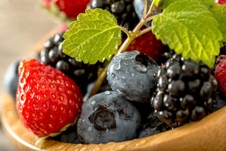 tilted: Close up tilted view on strawberries, blackberries and blueberries with little sprig of mint on top.