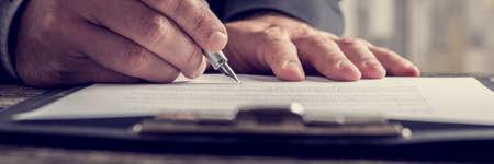 Retro effect vervaagde en afgezwakt beeld van een hand te schrijven op notitie papier aan klembord met pen, brede bijgesneden weergave. Stockfoto