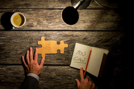you can: Conceptual image with inspirational message  You Can, of a man working on a puzzle on a rustic wooden table by the light of a lamp with coffee and a notebook with the handwritten words, overhead view.