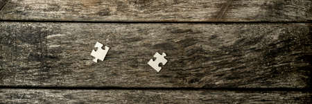 separate: Top down wide cropped view on two separate blank jigsaw puzzle pieces on old weathered wooden table. Stock Photo
