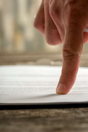 typed: In focus single human finger pointing to signature portion on typed out paper contract.