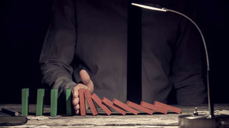 chain reaction: Conceptual image of the Domino Effect with a row of red dominoes falling intercepted by a mans hand preventing the chain reaction with green upright dominoes following on, close up view by lamp light. Stock Photo