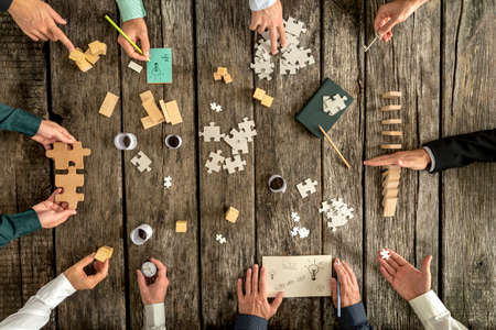 organizing: Business planning and brainstorming concept with a team of ten businessmen organizing strategy while holding puzzle pieces, writing down ideas on paper and rearranging wooden blocks, top view.