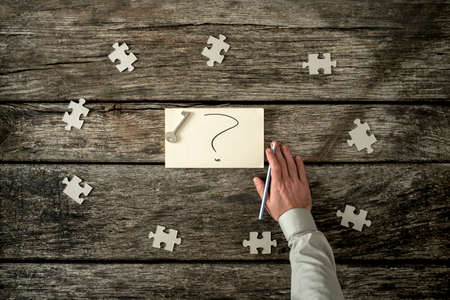 Eight blank puzzle pieces spaced evenly around hand written question mark near human arm holding pen over wooden table. Stock Photo