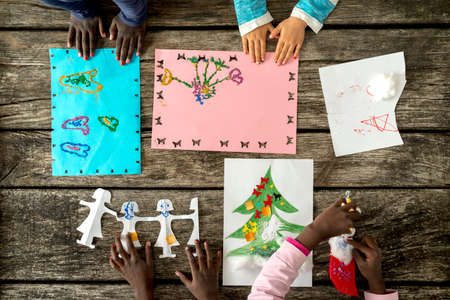 kids hand: Top down view on hands of unidentifiable children coloring on paper and making crafts over wooden table.