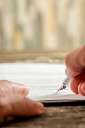 kugelschreiber: Extrem niedrige Winkelsicht auf hochwertigen Füllfederhalter in der Hand eigenhändige Unterschrift auf Papier zu schreiben.