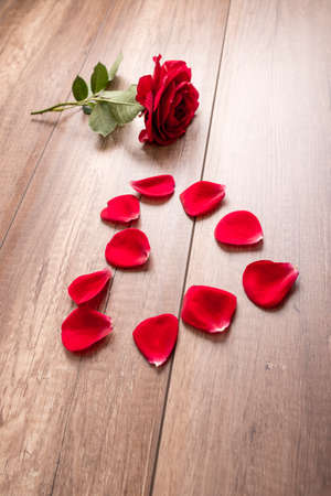 Single red rose and stem with ten separate petals formed in the shape of a heart on wooden table or floor. Stock Photo