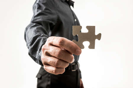 unidentifiable: Close up on hand of unidentifiable business man holding puzzle piece over neutral background for concept about solutions to problems.