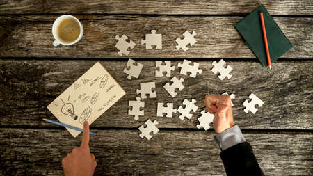 notecard: Top down view on thumb up and finger pointing to business symbols on notecard beside blank jigsaw puzzle pieces, checkbook and cup over old wooden table. Stock Photo