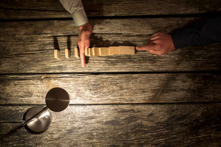 preventing: Businessman preventing the domino effect chain reaction by inserting his hand into a line of falling dominoes, overhead view on a rustic table lit by a single lamp with copy space.