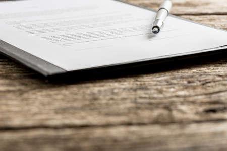 contratos: pluma destapada en la parte superior de la pieza a máquina de papel en el portapapeles. Incluye fuera de foco primer plano, con copia espacio. Foto de archivo