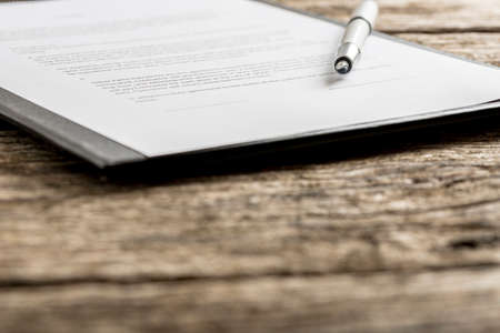 focus on the foreground: Uncapped pen on top of typewritten piece of paper on clipboard. Includes out of focus foreground with copy space. Stock Photo